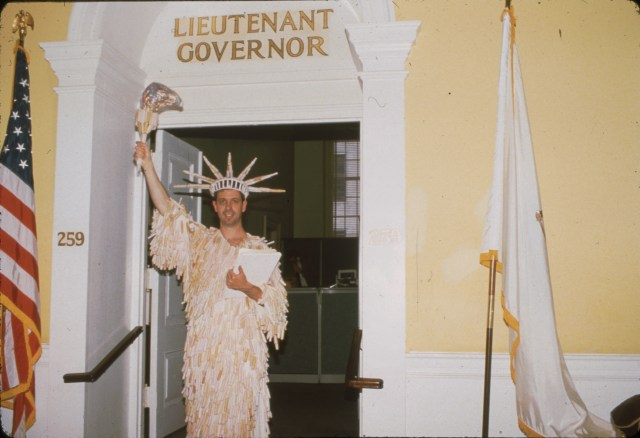 A person in a white Statue of liberty costume stands in a doorway, flanked by an American flag