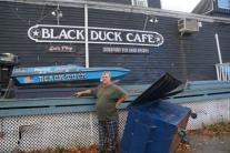"Original caption: ""Still afloat: Peter Aitkin, owner of the Black Duck, points to the high water mark from yesterday's flooding. Photo: Paul Schott"""