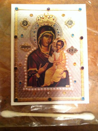 A cotton swab and icon, found in the home shrine of an interlocutor, were dipped in myrrh that flows from the Iveron icon of the Mother of God. Photograph taken by author and used with permission (2014).