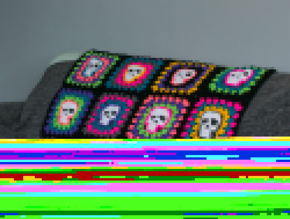 crochet blanket made with skull granny squares using brightly coloured yarn