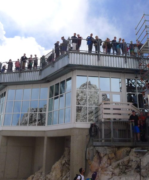 A group of tourists crowd the summit of Zugspitze