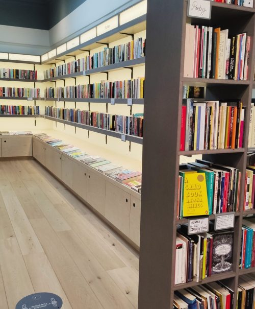 Modern white backlit shelves covered with books line the walls.