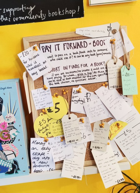 Pay it forward book pinboard at Lighthouse Bookshop. A brown corkboard against a yellow wall. Handwritten notices are stuck to it.