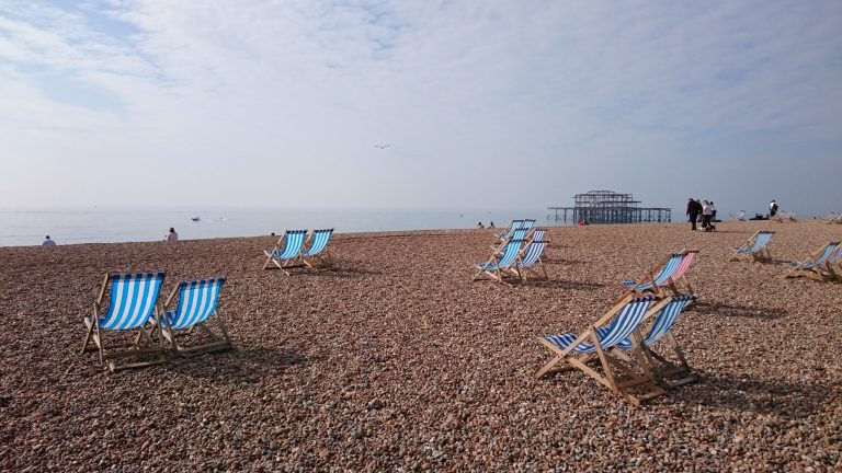 Striped blue and white deckchairs sit in pairs on a pebbled beach