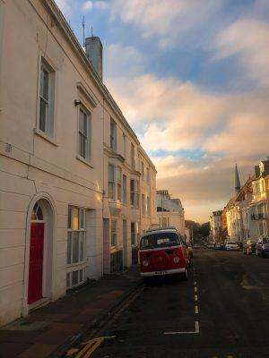 Terrace houses line the sides of a street. A vintage red campervan is parked outside a red door
