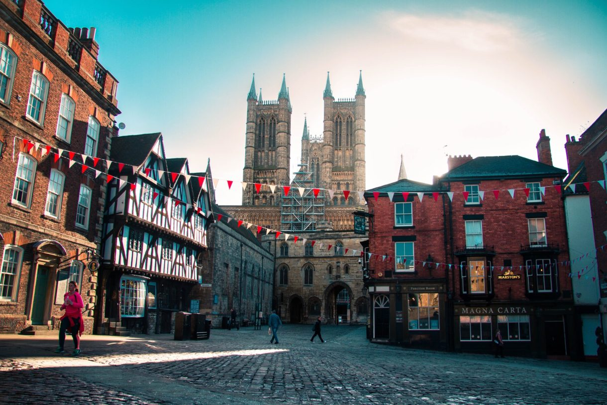 A cobbled street square. Red and white triangle flags are strung across the square. Lincoln cathedral stands in the background
