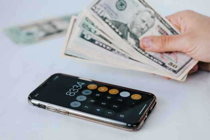 crop faceless person with cash and calculator app on smartphone