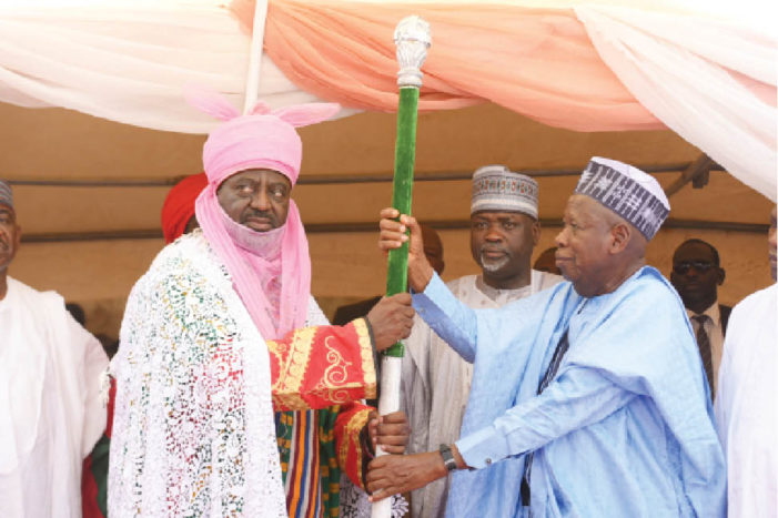 Governor Ganduje presenting staff of office to one of the new emirs of Kano