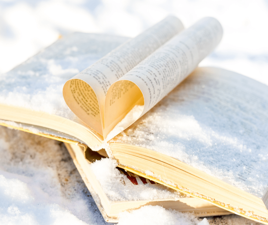 Open book in the snow with center pages folded together to create a heart