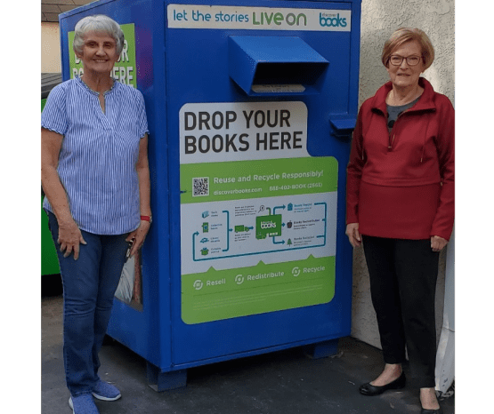 """Two ladies standing next to our blue book collection box. The sticker on the box says """"Drop Your Books Here."""""""
