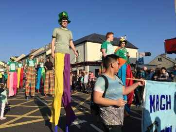 Saul Gavigan and stilt walkers from Magh Ene College