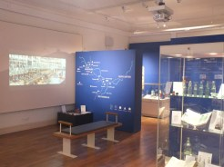 Room with various information displays with a glass display case in the foreground
