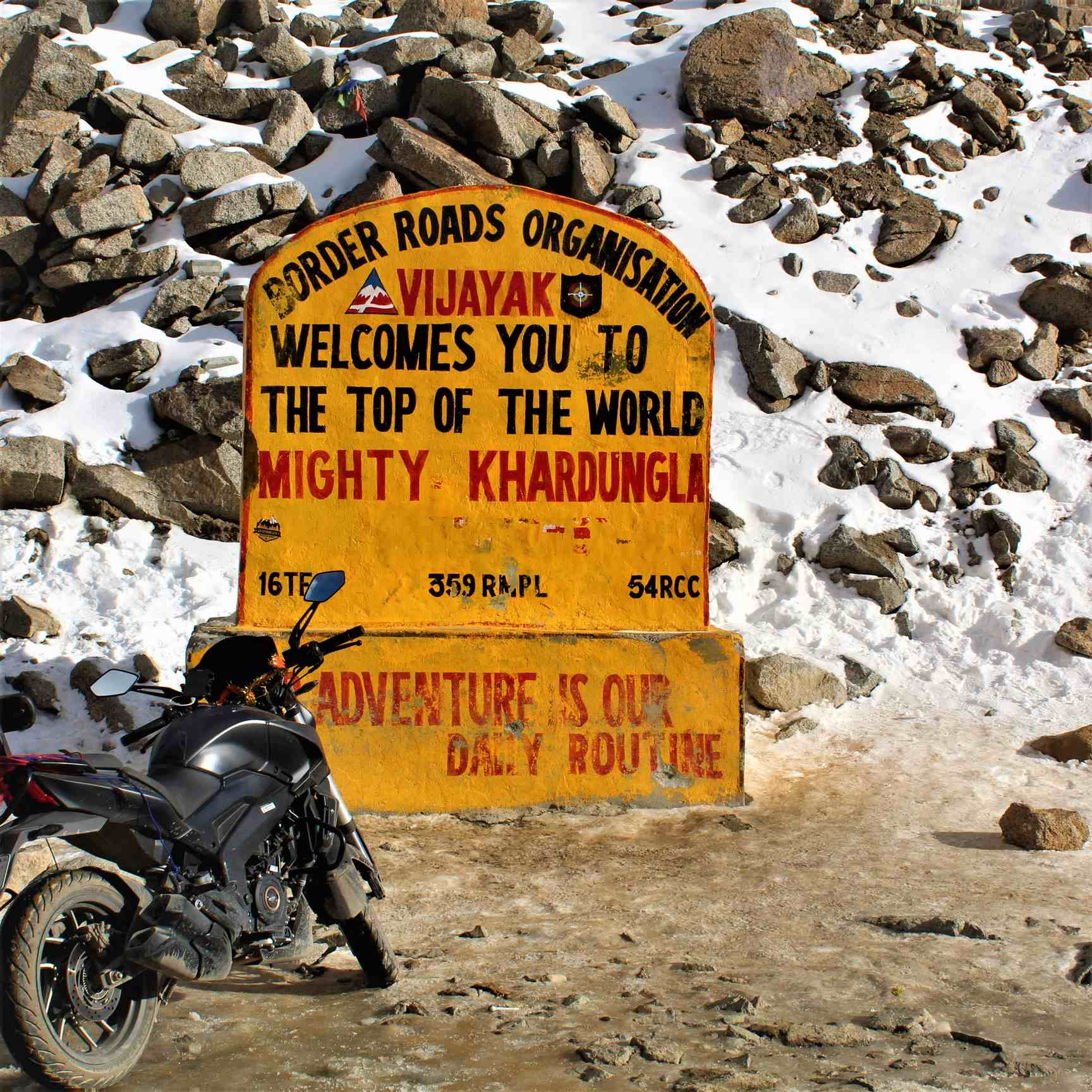 Kardungla pass sign with bike parked aside.