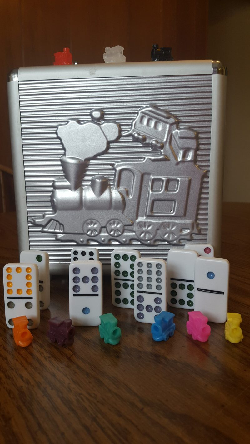 Mexican Train Dominoes case with dominoes and trains in front