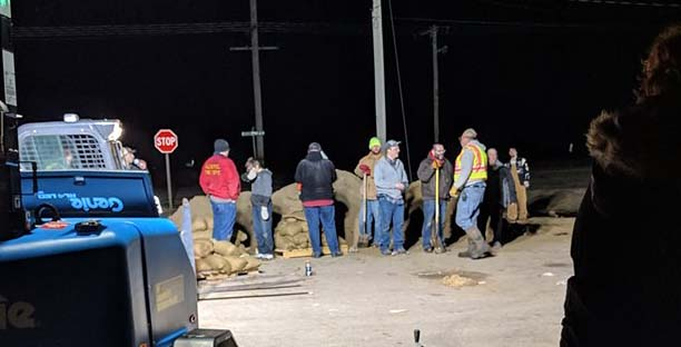 How to help after a natural disaster: during a disaster sandbagging a small village about to flood during the night