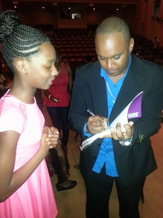 Montserrat Idol winner Prince Romeo signs an autograph for a fan.