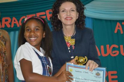 Summer-Rae Gibbons was first in the Grade 2 category. She receives her certificate and trophy from Her Excellency the Governor, Elizabeth Carriere.