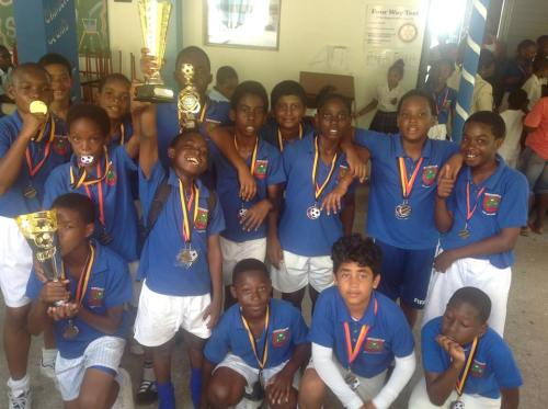 St Augustine boys' football and cricket team show off their trophy and medals. (Wannis Persaud Photo)