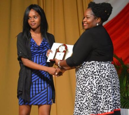 Top CAPE student Sharline Gibbons receives her award from Hon. Minister of Education Delmaude Ryan.