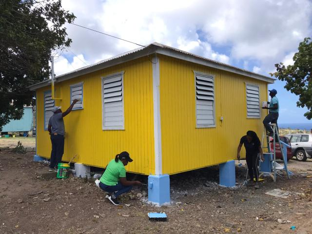 Wooden house being painted yellow
