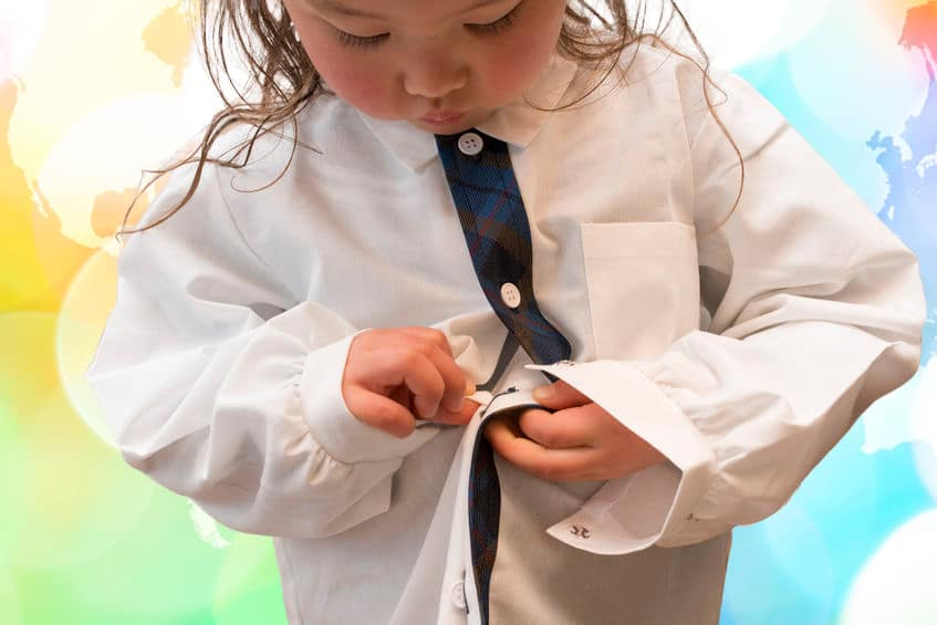 Fine motor development- self-confidence-independence-young girl working to button her shirt