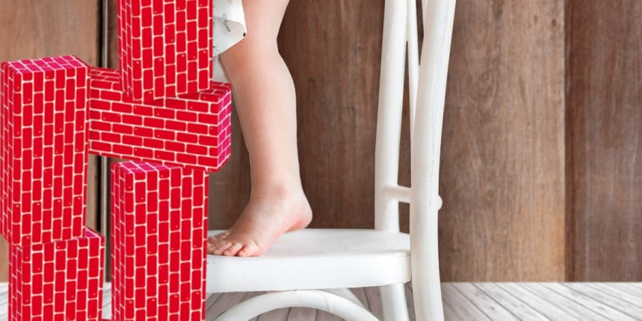 jumbo blocks-build it big-take building to new heights-little girl standing on a chair stacking giant red cardboard brick blocks