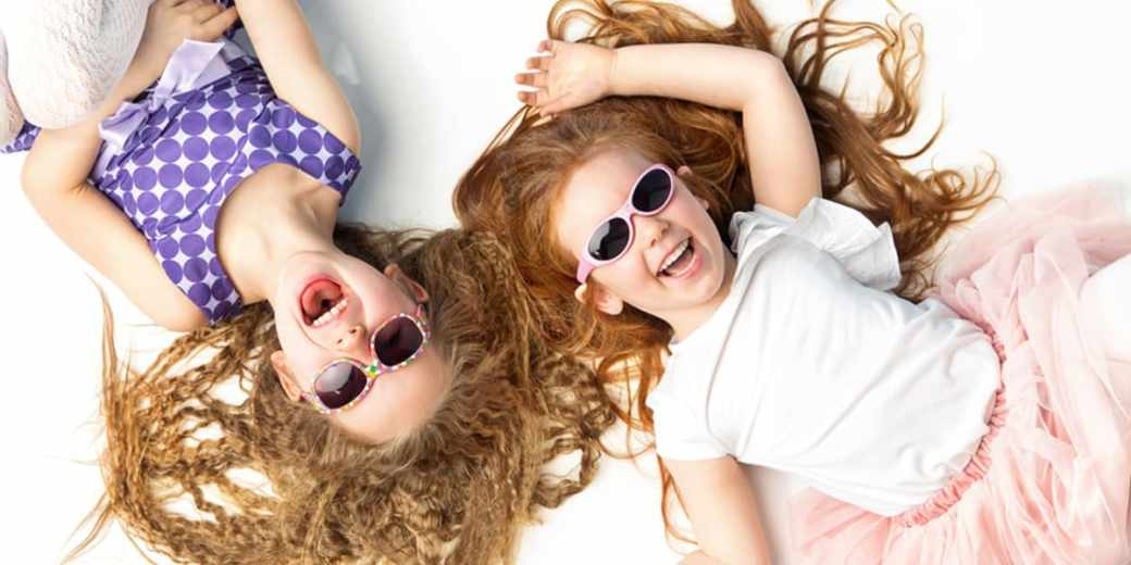 kids imagination-twin girls lying face up on the floor giggling