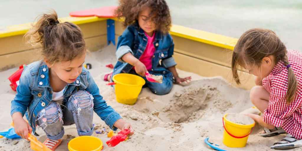 constructive play-3 girls playing in the sand box