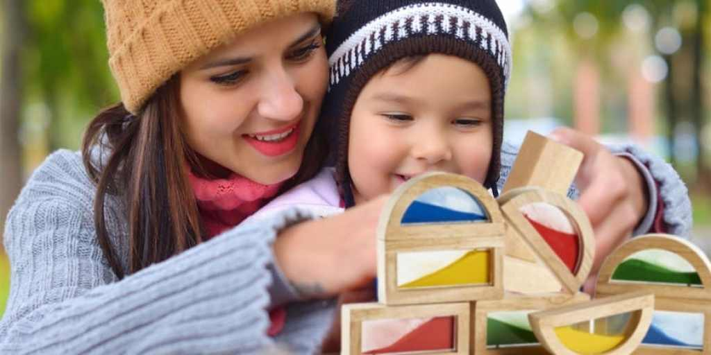constructive play-mother and son playing with wooden stacking blocks