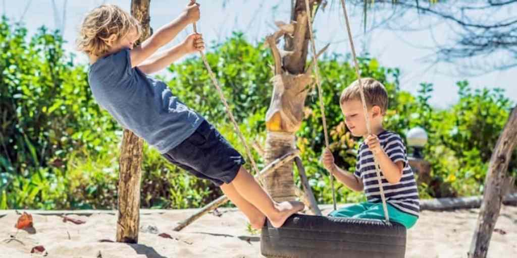 gross motor activities-two young boys playing on a tire swing in the sunshine