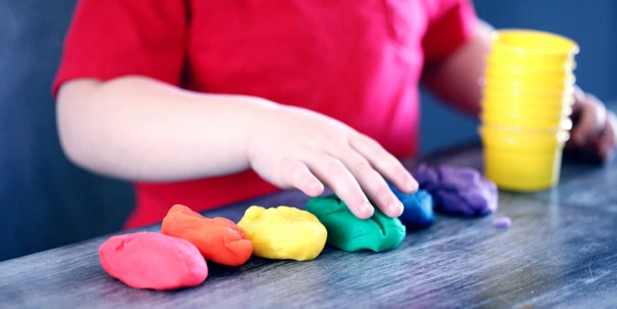 language activities for preschoolers-preschool boy playing with rainbow colors playdough