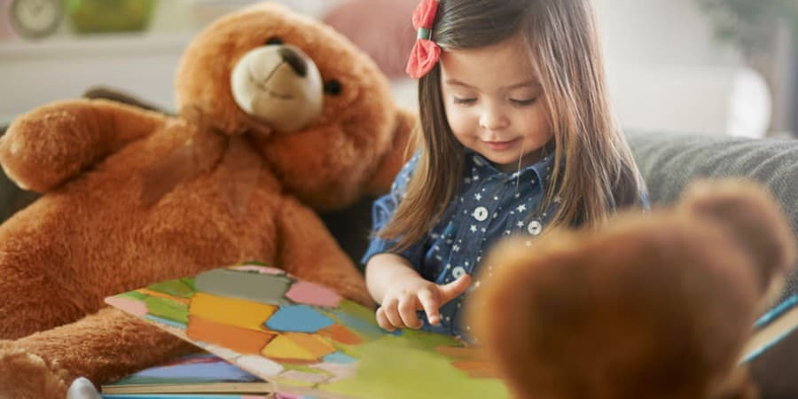 language activities for preschoolers-storytelling-young girl telling stories to her stuffed bears