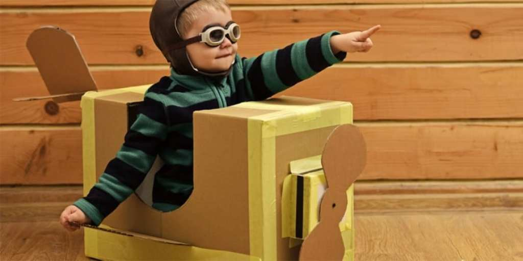 language development and imaginative play-toddler boy dressed as a pilot in a plane made from a cardboard box
