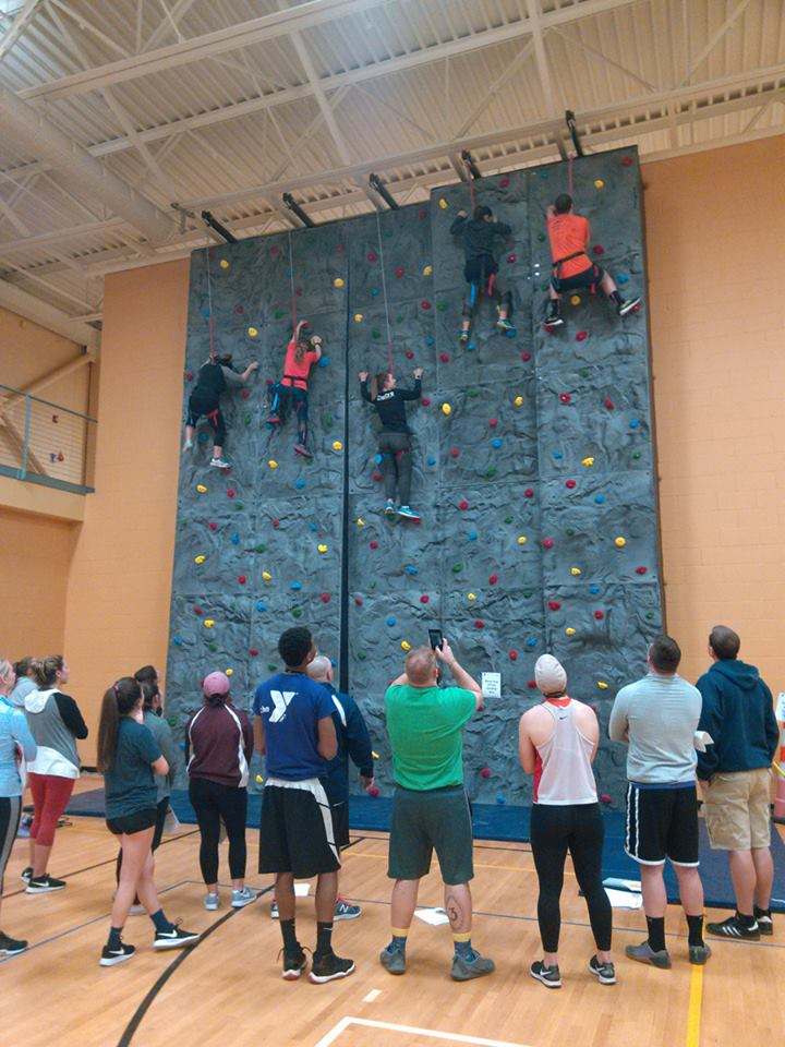 5 adults climbing on the indoor wall