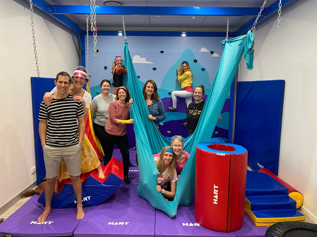 A therapy centre in front of a bouldering wall.