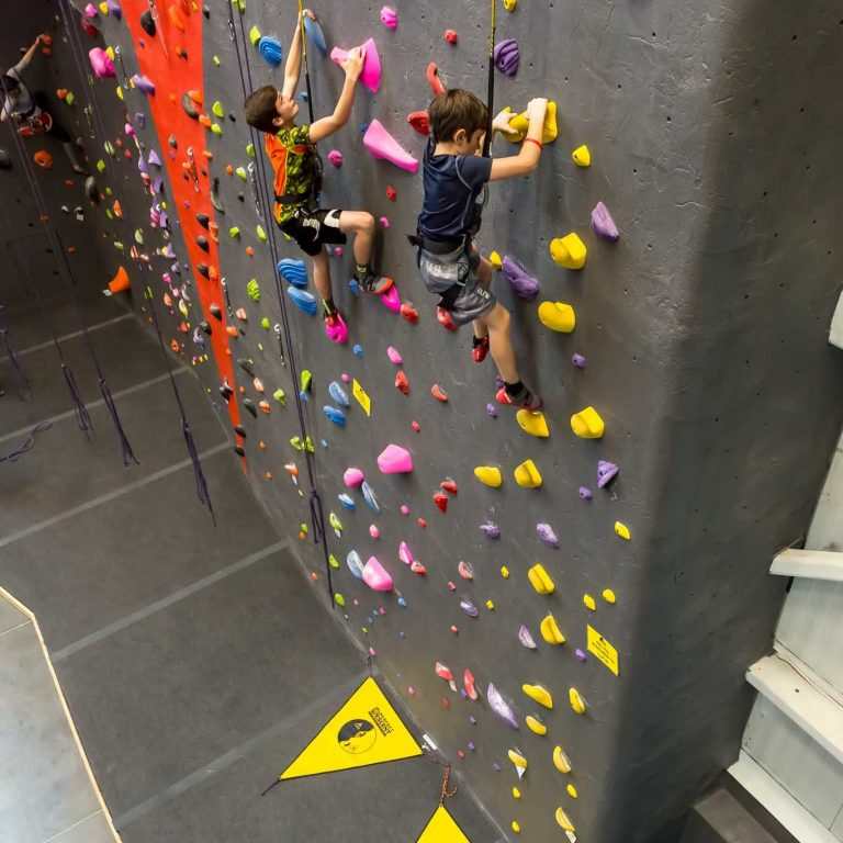 2 kids climbing on the perfect descent auto belays