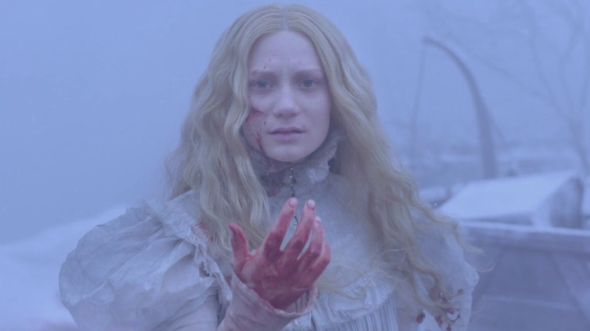 Mia Wasikowska with a bloodied hand stands in the crystal white snow of Crimson Peak.