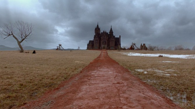 A red clay road leads up to the haunting manor of Crimson Peak under a gray sky.