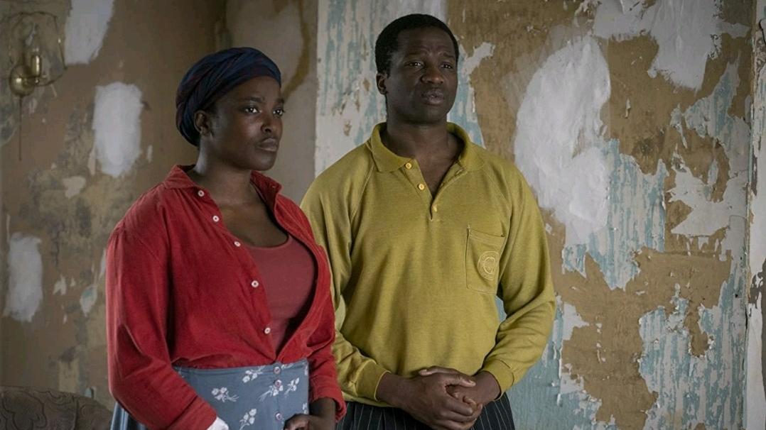 Sope Disiru and Wunmi Mosaku stand patiently in a torn down apartment as seen in His House.