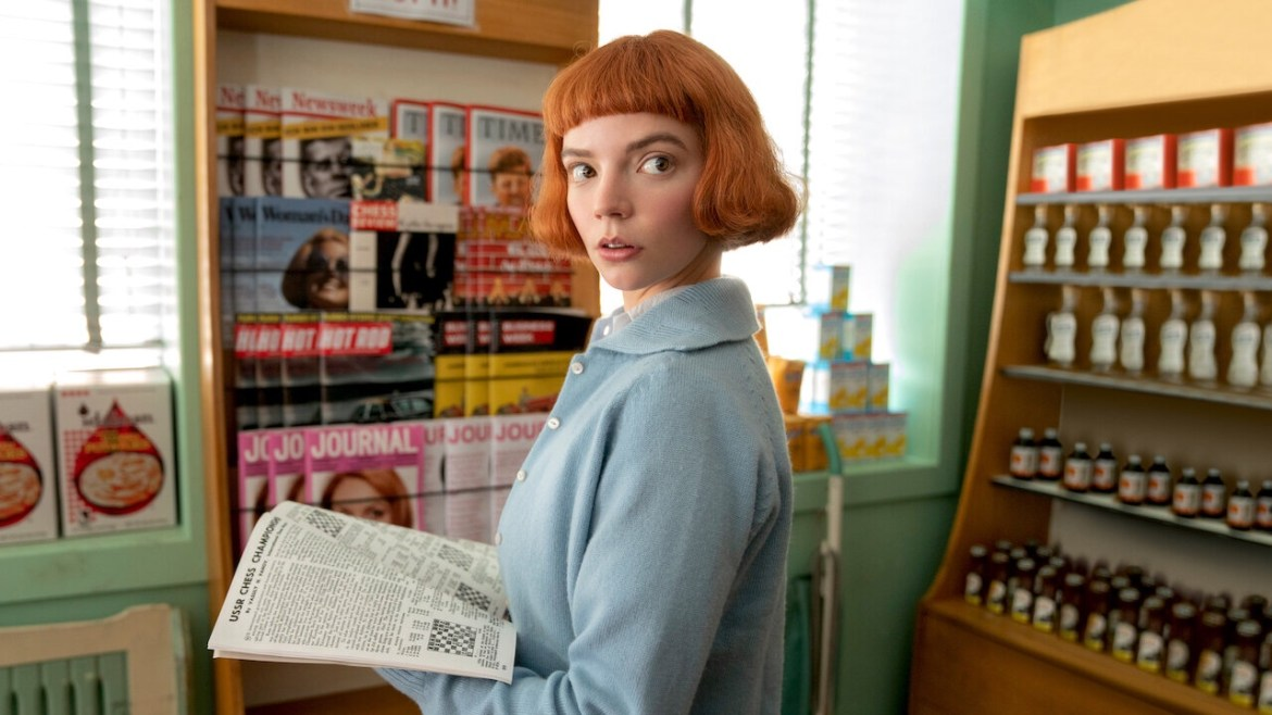Anya Taylor-Joy poses by a newspaper stand in 'The Queen's Gambit.'