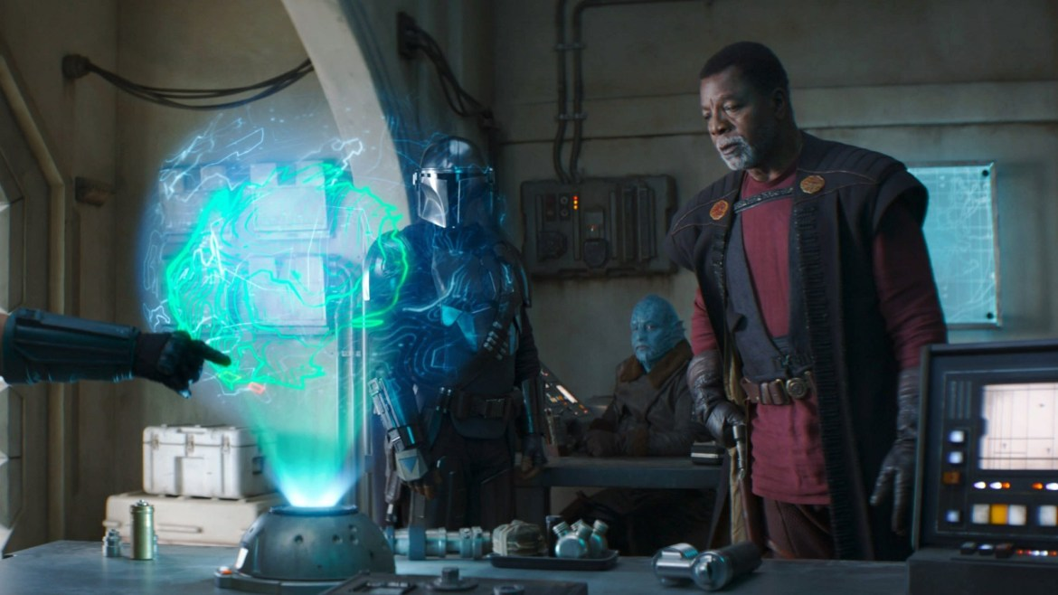 Carl Weathers as Greef Karga inspects a holographic map with Pedro Pascal's title character as seen in Chapter 12 of The Mandalorian.