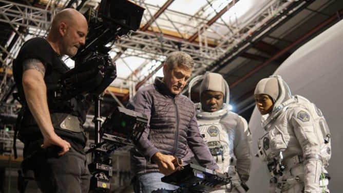 George Clooney directs a space scene with David Oyelowo and Tiffany Boone in astronaut suits on the set of The Midnight Sky.