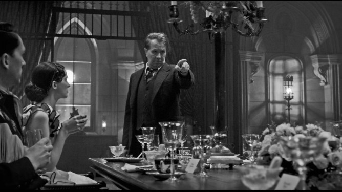 Gary Oldman as Herman J. Mankiewicz pointing his finger at a grand dinner table as seen in Mank.
