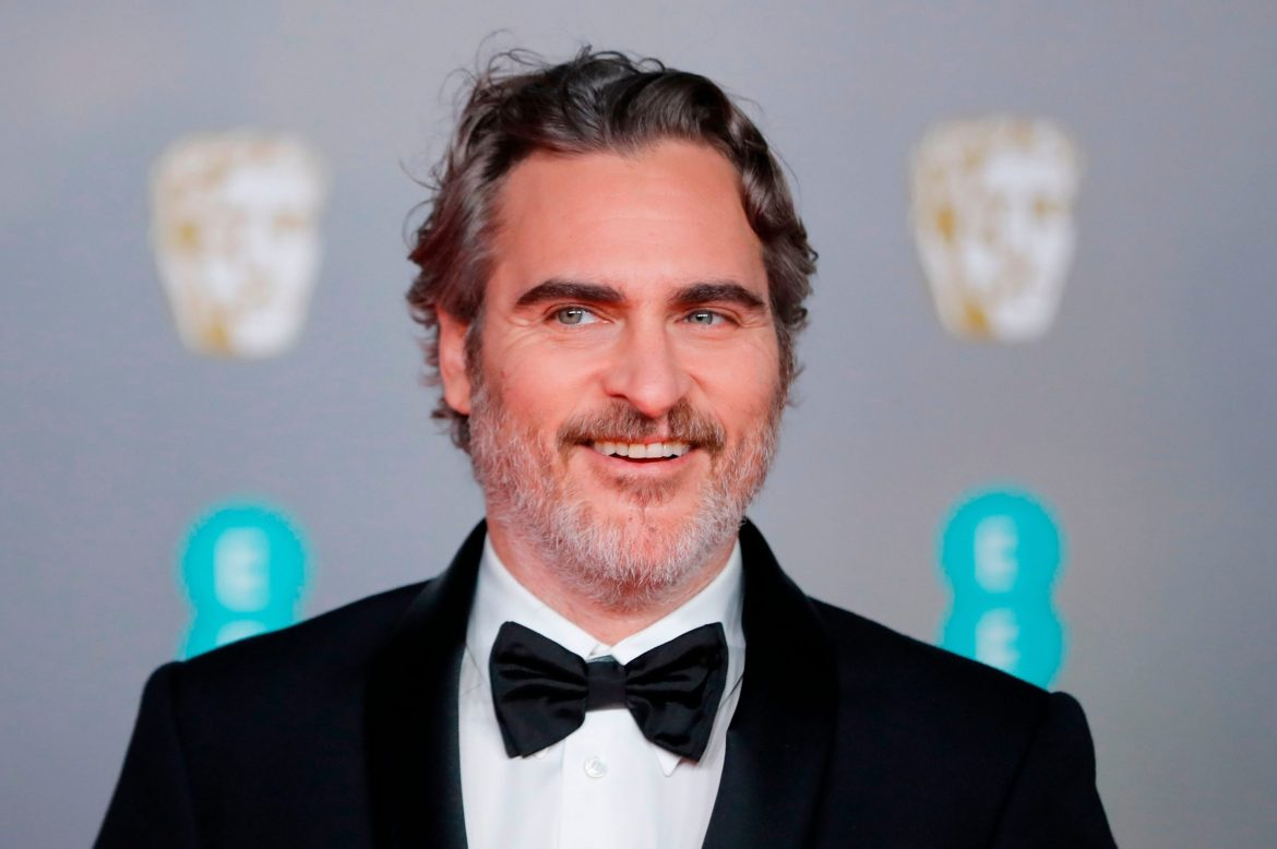 Joaquin Phoenix smiles as he wears a suit and bow tie on a BAFTA red carpet event.