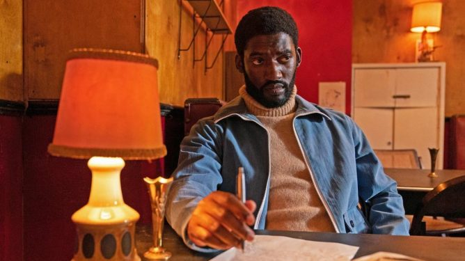 Malachi Kirby as Darcus Howe does work at a table as seen in Steve McQueen's Small Axe Anthology.