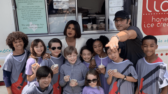 Robert Rodriguez and the child cast of We Can Be Heroes group together for a photo on set.