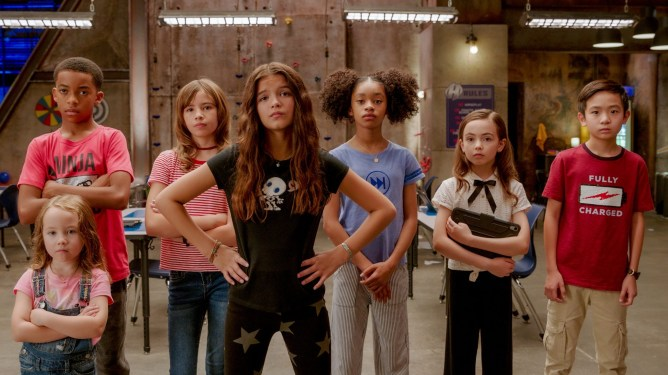 Vivien Blair as Guppy, Isaiah Russell-Bailey as Rewind, Lotus Blossom as A Capella, YaYa Gosselin as Missy Moreno, Akira Akbar as Fast Forward, Hala Finley as Ojo, Dylan Henry Lau as Slo-Mo standing as a team as seen in We Can Be Heroes directed by Robert Rodriguez.