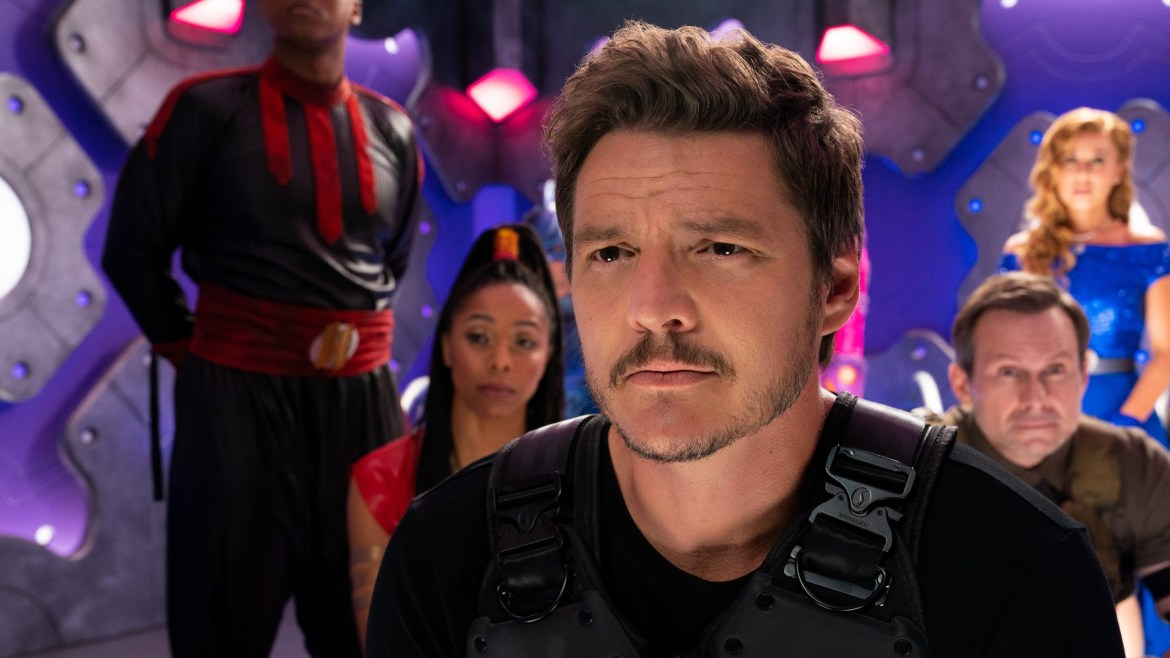 Pedro Pascal sitting in a room with his fellow imprisoned heroes as seen in We Can Be Heroes on Netflix.