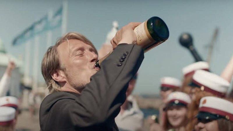 Mads Mikkelsen drinking a bottle of champagne in Another Round which makes our list of best films of 2020.