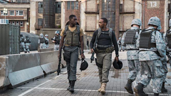 Damson Idris and Anthony Mackie walk alongside U.S soldiers in a futuristic base as seen in Outside the Wire.